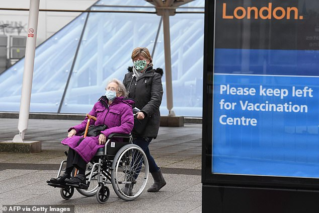 Mavis, 87, is pushed by her daughter out of the Covid-19 vaccination centre at ExCel London, home to the London Nightingale Hospital, in London