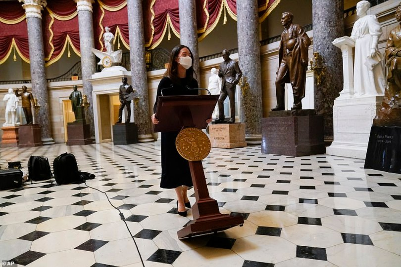 A lectern belonging to Speaker of the House Nancy Pelosi is moved through Statuary Hall for a news conference Wednesday. The news conference is scheduled after a vote on an article of impeachment against President Donald Trump