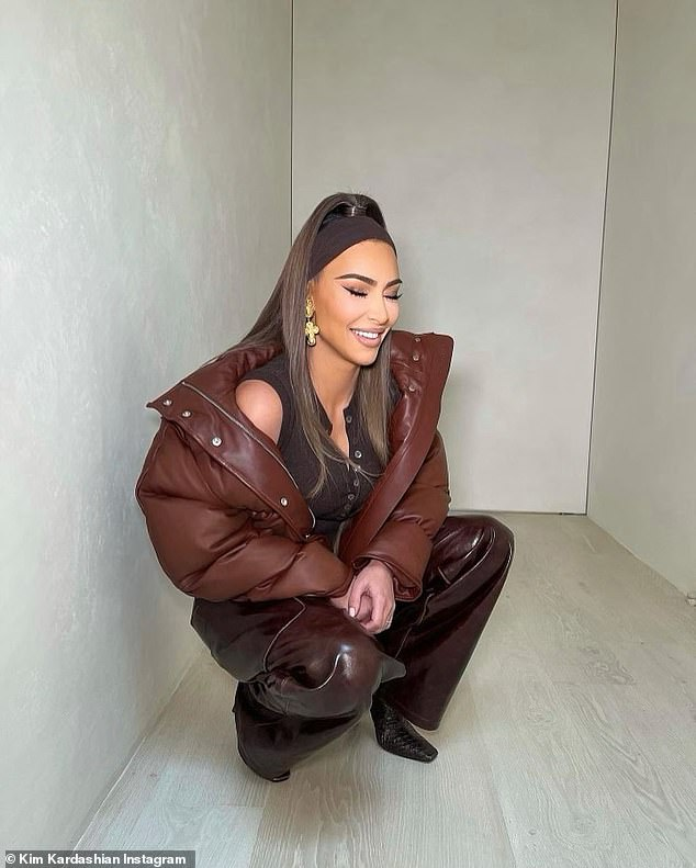 Say cheese! The SKIMS mogul beamed with joy as she crouched to the floor in her leather trousers