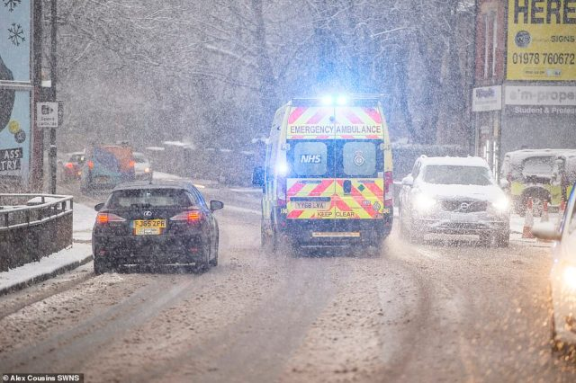 An ambulance makes its way along a snowy road today during blizzards in Leeds as flurries hit the West Yorkshire city