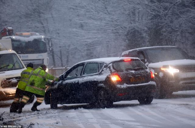 Two people push a stranded car on a snowy road in West Yorkshire today as motorists drive through Pool-in-Wharfedale