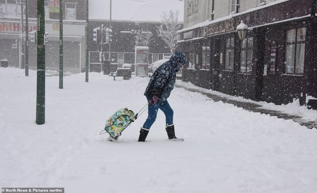 A shopper struggles to drag their trolley through thick snow at Consett in County Durham this morning