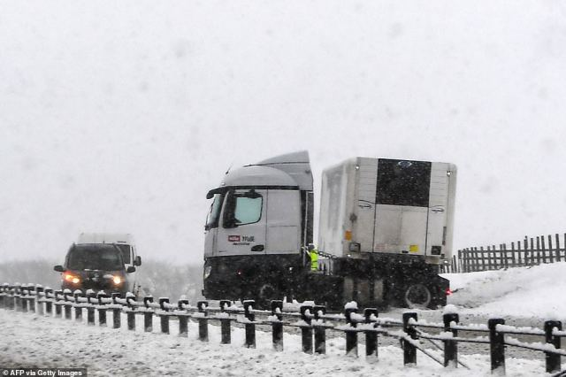 A lorry sits jackknifed on the southbound A9 road near Gleneagles as heavy snow falls on parts of Scotland this morning