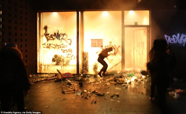 A police station was set on fire (pictured) with other pictures showing fires had been lit in the streets of the city