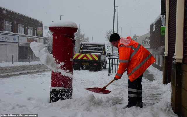 Council workmen clear snow from the high street in Consett, County Durham  this morning as the flurries continue