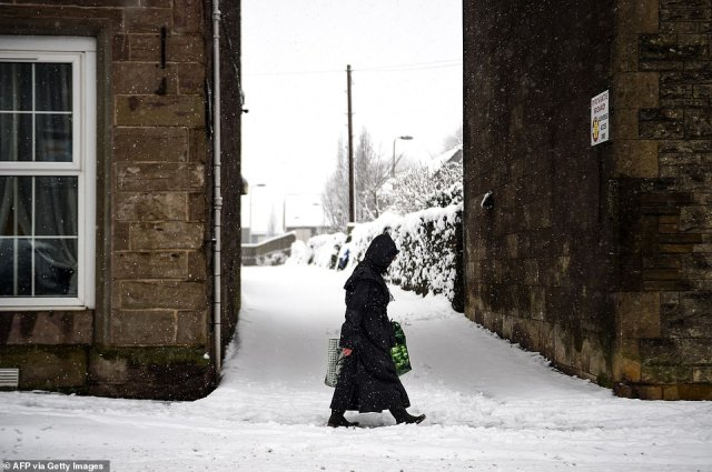 A pedestrian walks along a snow-covered pavement today in Auchterarder, a town in Perth and Kinross, Scotland