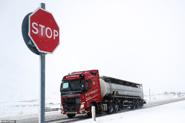 A truck makes its way through the Pass of Drumochter in Scotland today as heavy snow falls in the area