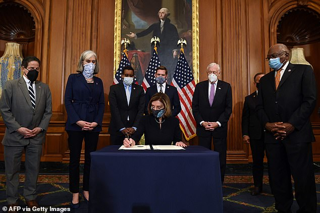 House Speaker Nancy Pelosi signs the article of impeachment against President Donald Trump at an engrossment ceremony after the vote Wednesday night