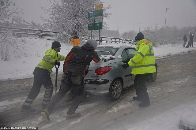 Drivers are caught in the snow in the village of Ainley Top in Calderdale, West Yorkshire, this afternoon