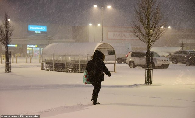 A shopper makes her way across the Morrisons car park in Consett, County Durham, as the snow continues to fall today