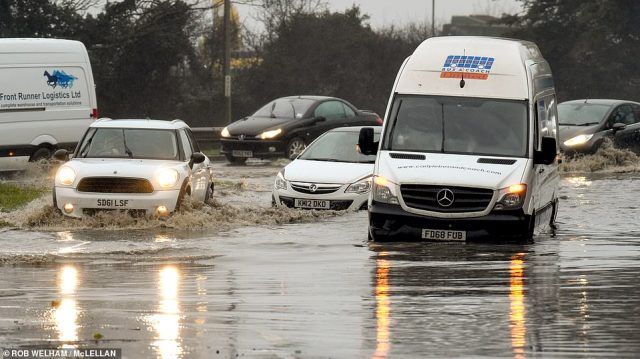 Cars make their way past a van stuck in floodwater after rain caused flooding on the A127 near Brentwood in Essex today