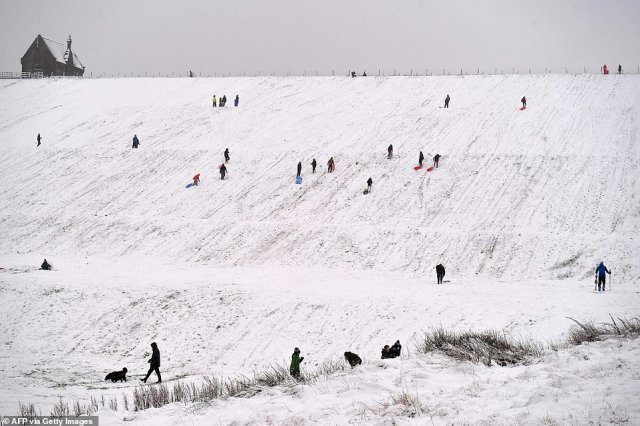 People sledge down a hillside at Butterley Reservoir in Marsden, northern England