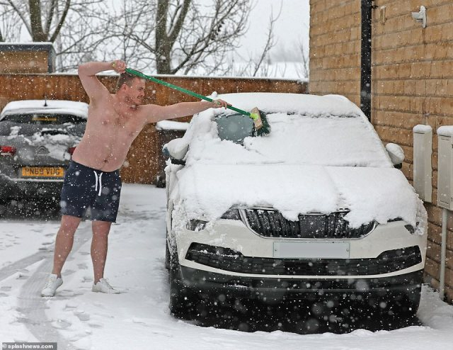 A man sweeps snow off his car windscreen with a broom while wearing only his shorts and shoes in Wakefield today
