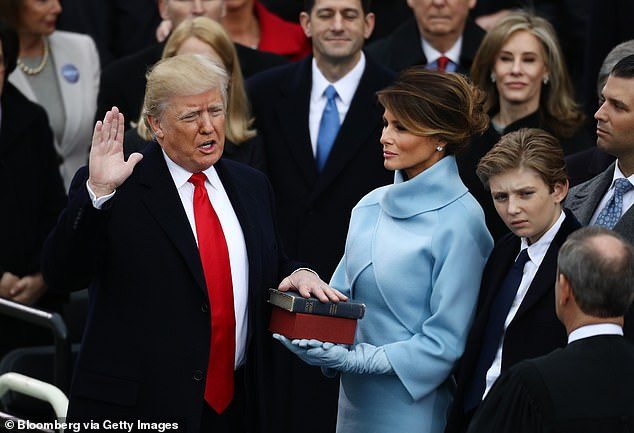 Melania Trump found out she was not going to Joe Biden's inauguration when President Trump tweeted he would not attend - above she holds the bible while Trump takes the oath of office at his January 2017 ceremony
