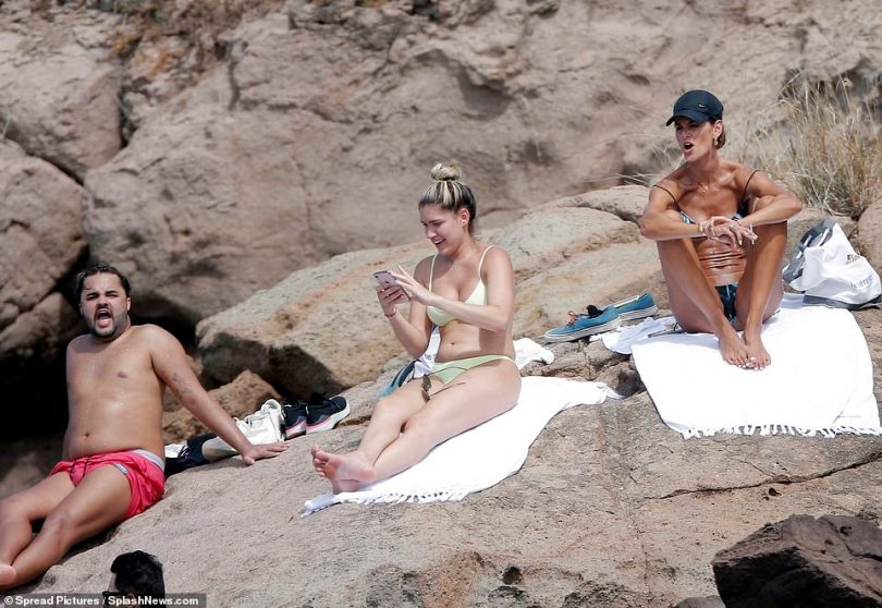 Friends on the beach: Izabel could be seen relaxing in the sunshine with her group of pals after they jetted abroad for the break, includin Lucas Guedez (pictured far left)