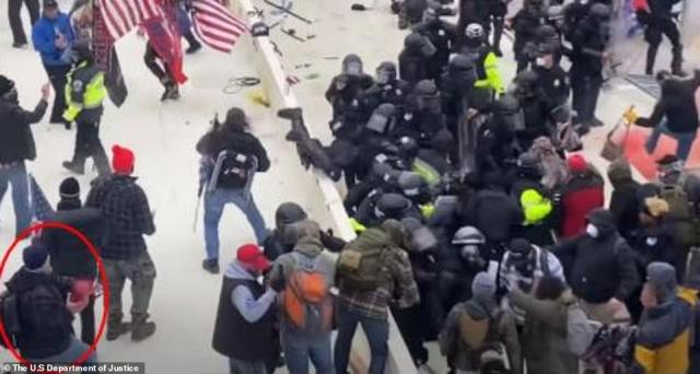 An affidavit filed in connection with Sanford's arrest states that the incident was caught on video at about 2.30pm during the riots on January 6. A screengrab from the video, which was included in the affidavit, is shown above, with Sanford circled in red