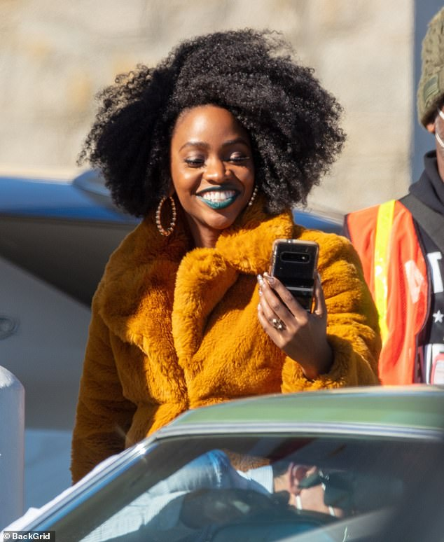 Texting away: As she stood by the passenger seat of Boyega's vintage car, the 33-year-old Dear White People actress rocked a bright blue lipstick and orange fur coat