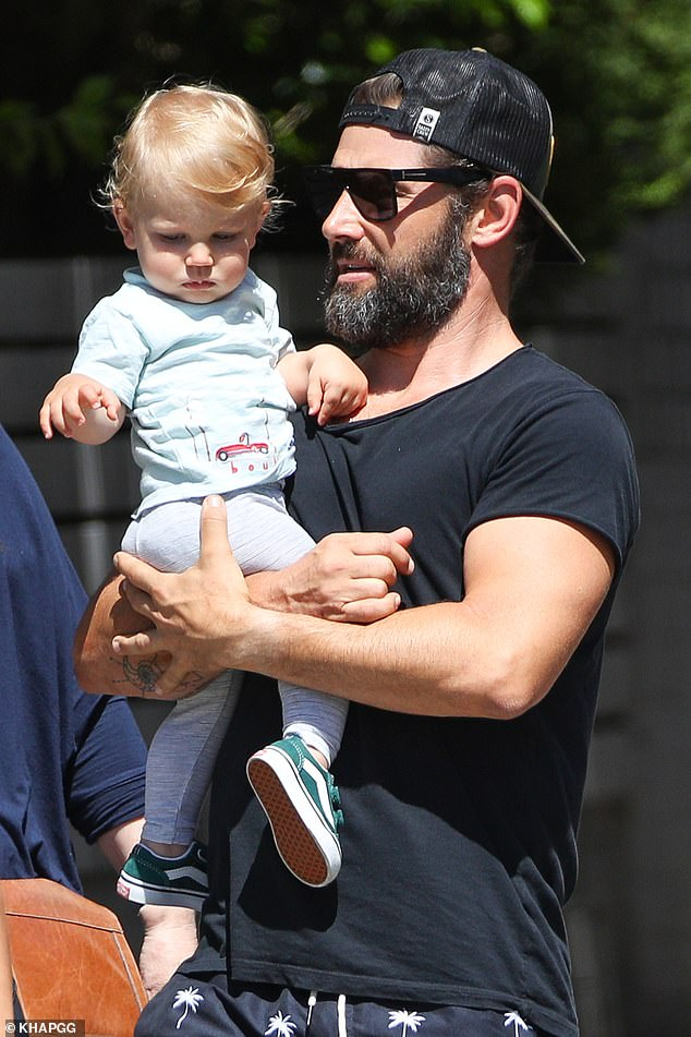 Dad's boy: He carried little Austin who looked adorable in his light blue T-shirt with grey trousers and green baby Vans sneakers