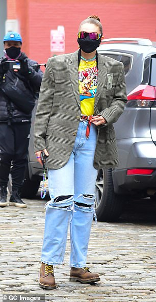 Stepping out: Gigi paired her jacket with lightwash jeans, which featured distressed features at the knees, and gave it a punk chic temperament by wearing brown lace-up shoes