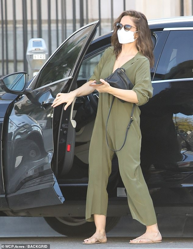 Chic: Minka wore a flowing olive-colored jumpsuit with a plunging neckline, which she wore with understated brown thongs