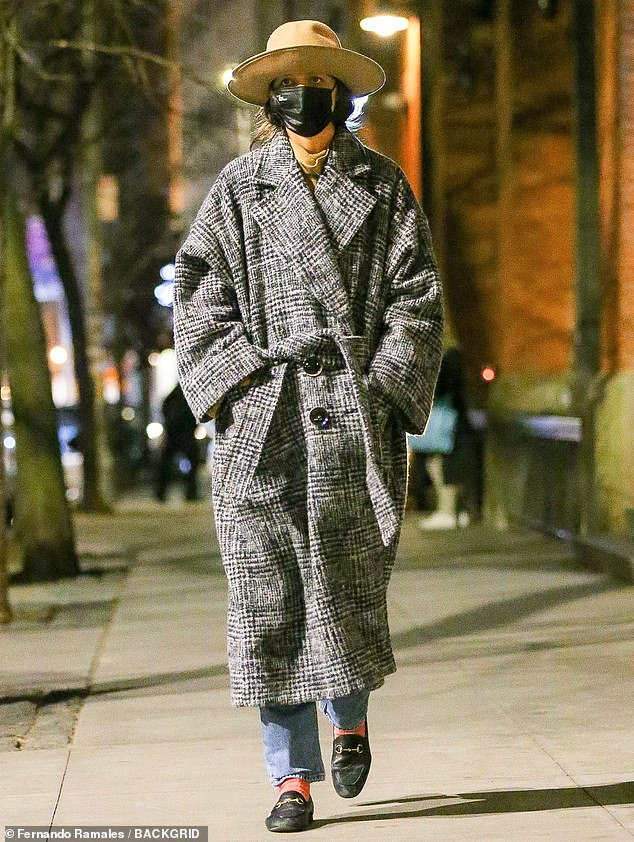 Late night stroll: Katie Holmes, 42, took in the nighttime air on a solo evening stroll in NYC as she sports a fashionable grey coat and an oversized tan hat