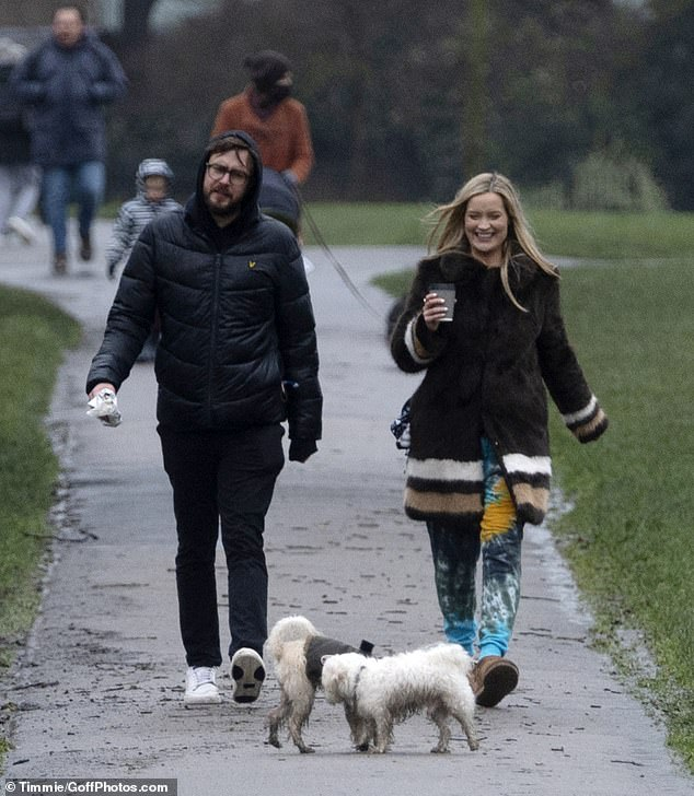 Out and about! Laura Whitmore and her other half were seen enjoying a brisk walk earlier this week, as they took their dog Mick out in London