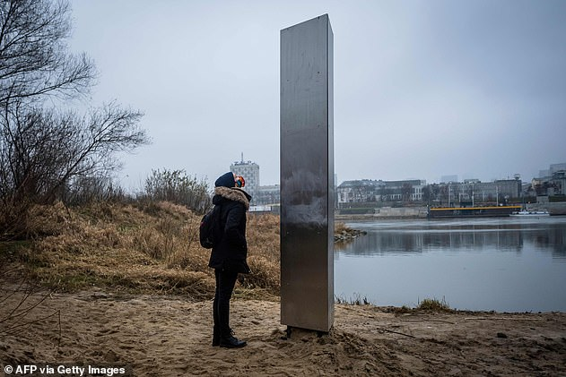 A woman contemplates a strange monolith that appeared on December 10 in Warsaw, Poland