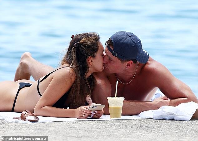 New boyfriend? Bachelor finalist Bella Varelis (L) enjoyed a steamy lip kiss with photographer Will Stokoe (R) as she stripped down to a skimpy black bikini at Balmoral Beach on Sunday