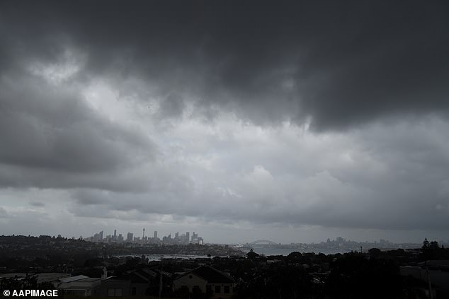 Sydney was in for a shower or two on Tuesday but the weather will warm up later in the week, reaching 43C by Monday in the city's west. Pictured, storm clouds in Sydney on Tuesday