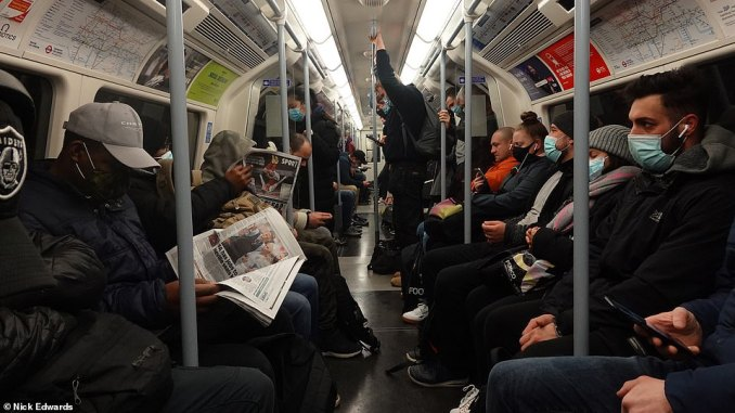 Passengers sit and stand on a Jubilee line train in East London this morning as key workers continue to travel in to work