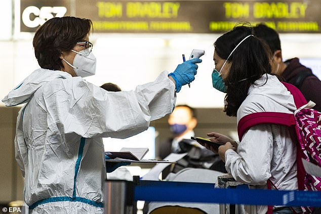 Passengers will have their temperature taken by a technician from local health care group, Mercy Medical Center, and fill out a questionnaire. Pictured: Travelers are screened and have their temperature checked by airline employees as they check in luggages at Los Angeles International Airport, November 24