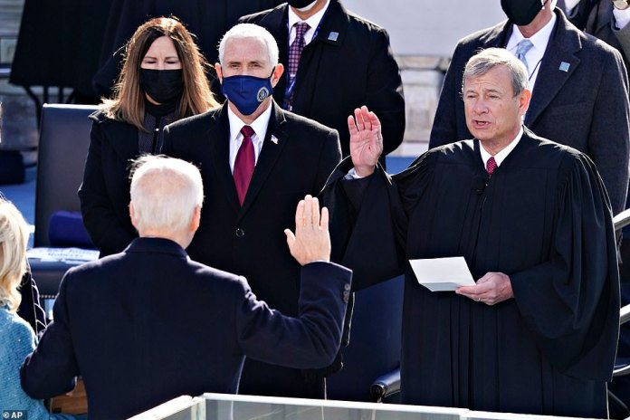 Transfer of power: Pence, at the back, watches Biden recite the oath with Chief Justice John Roberts on the steps of the Capitol on Wednesday, after Trump boycotted the inauguration