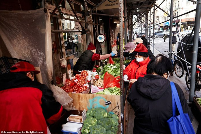NEW YORK CITY:Shoppers in December remain masked and on the street as vendors set up outside