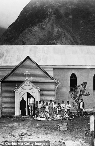 Father Damien (1840–1889) stands with patients outside his church on Molokai Island.  He served in the island's leper colony, eventually contracting the disease himself