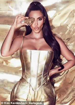 Stunning: Kim has also created a stunning gold version of the same outfit, with a slim corset that adds more attention to her slimline waist.