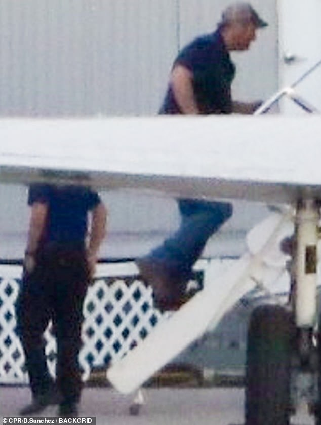 In transit: The 44-year-old steamboat was seen showing off his toned arms in a navy polo shirt as he boarded a private jet
