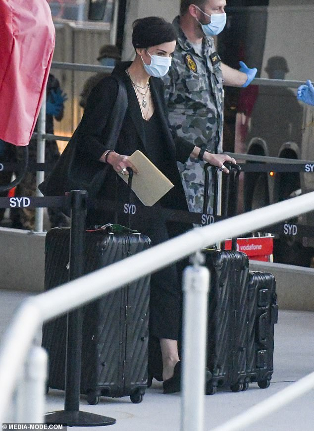 Hidden: The 36-year-old looked to be in a good mood as she left the airport with a face mask