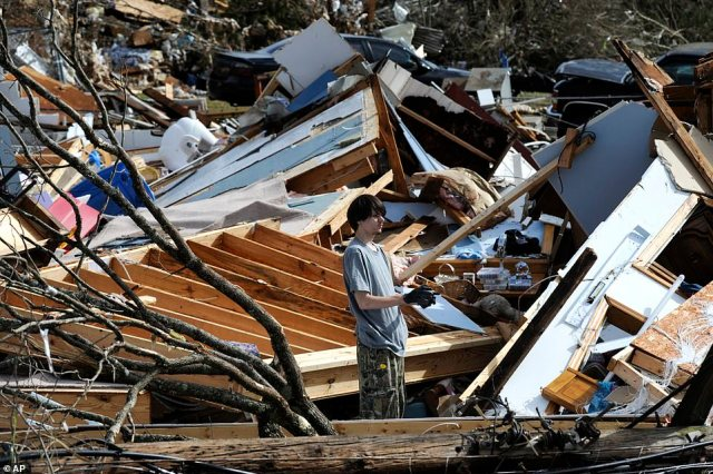 James Scott wears gloves while he picks through the remains of his home after it was leveled by the tornado