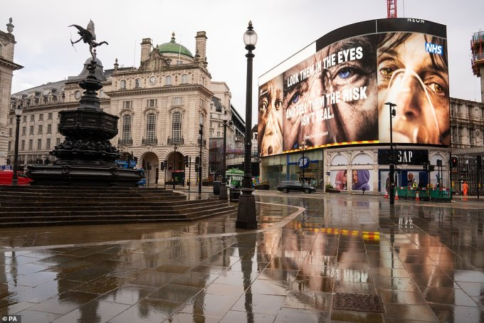 A government coronavirus advert on the big screen at a near deserted Piccadilly Circus in London, pictured today