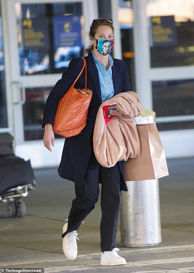 No personal assistant seen: The star added a Ruth Bader Ginsburg face mask with her hair pulled back and glasses on her head. Over her shoulder was an orange taxi purse. She also carried an overcoat and a bag