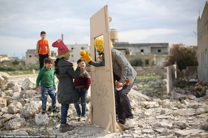 This heartwarming - and heartbreaking - image was taken by Syrian Mouneb Taim in Saraqib, Syria. It shows puppeteer Walid Rashed performing for children. Since 2013 he has been touring refugee camps and devastated neighbourhoods with his act
