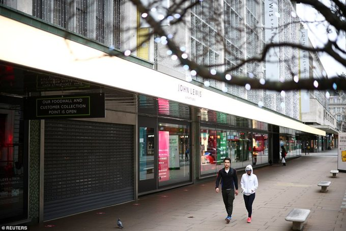 People walk along Oxford Street next to shutters at the flagship John Lewis store as non-essential shops remain closed