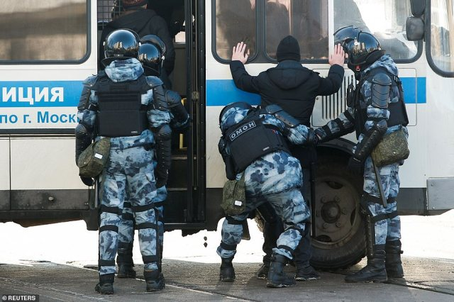 Law enforcement officers detain Navalny supporters close to the court building this morning
