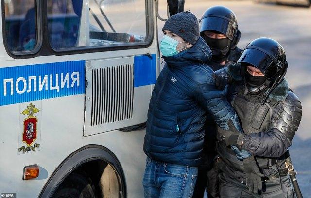Riot police push a demonstrator towards their van
