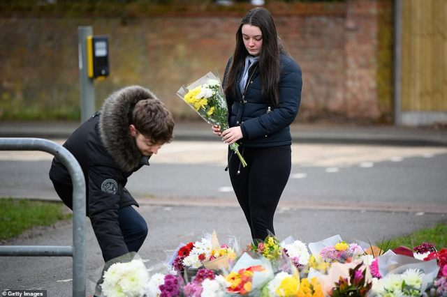 Well-wishers lay flowers outside Captain Tom's home in Bedford this morning after his death yesterday aged 100