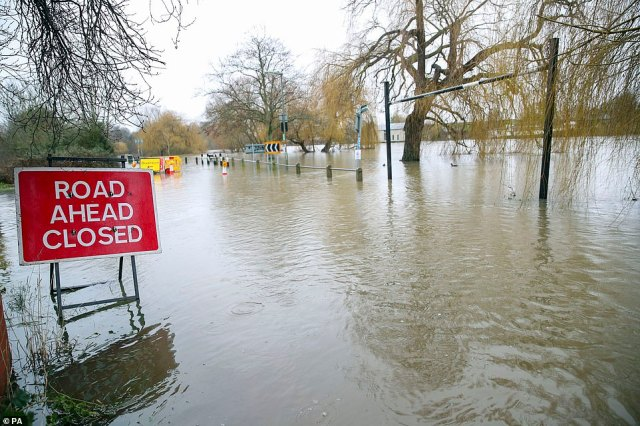 A flooded road in Laleham-on-Thames, Surrey, today after the banks of the River Thames burst