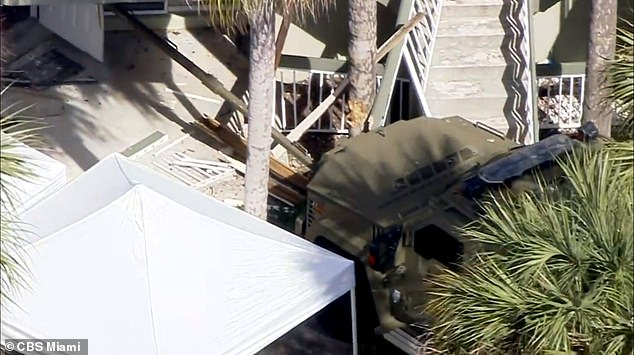 The suspect, who was armed with an assault-style rifle, lay in wait for the FBI agents and opened fire on them through his unopened door after observing them through the doorbell camera. Pictured above is a SWAT vehicle that appeared to have crashed through barricades at the apartment