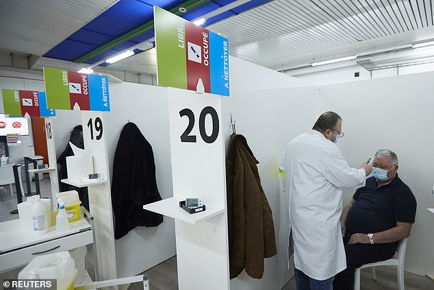 Switzerland has refused to approve the Oxford AstraZeneca vaccine amid concerns over insufficient data and regulators said 'new studies' were needed. Pictured: A medic checks a man's temperature at a vaccination centre in Geneva, Switzerland