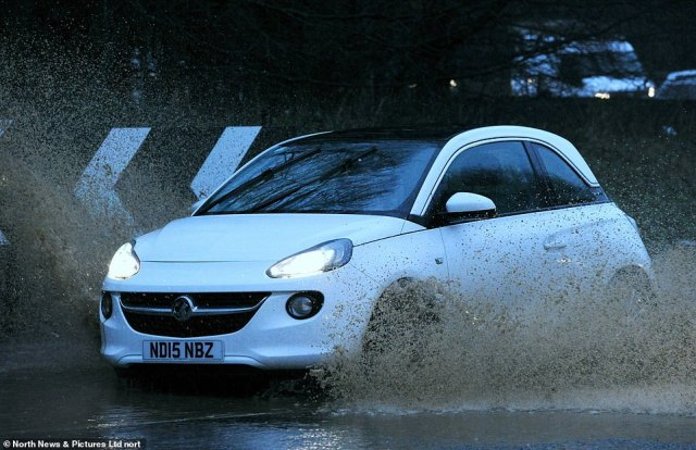 A car splashes through floodwater in Sunderland today as the Environment Agency issued more than 200 alerts or warnings