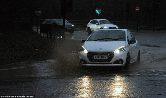 A car drives through floodwater in Sunderland today after a section of the A19 northbound had to be closed